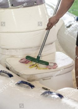 stock-photo-man-washing-white-inflatable-boat-with-brush-and-pressure-water-system-at-garage-ship-service-and-1329482348